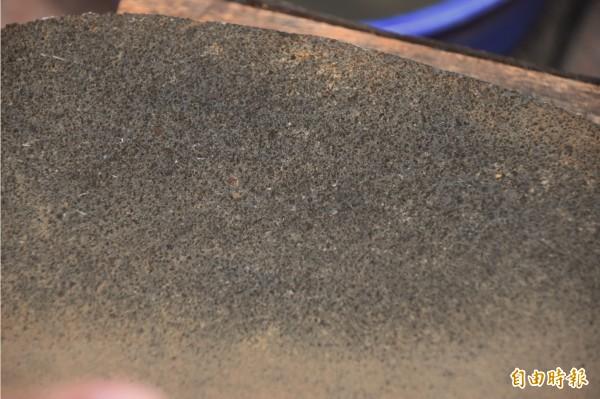 巴圖形石器表面有很多小凸起黑點,依顏色推判,應是玄武岩特徵。(記者蘇福男攝)