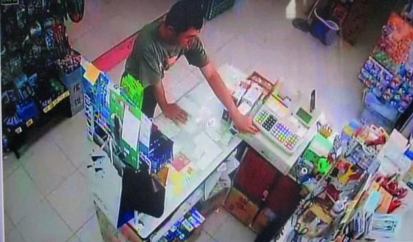 林姓男子趁店員不在,伸手偷拿收銀機裡的50元硬幣。(記者陳祐誠翻攝)