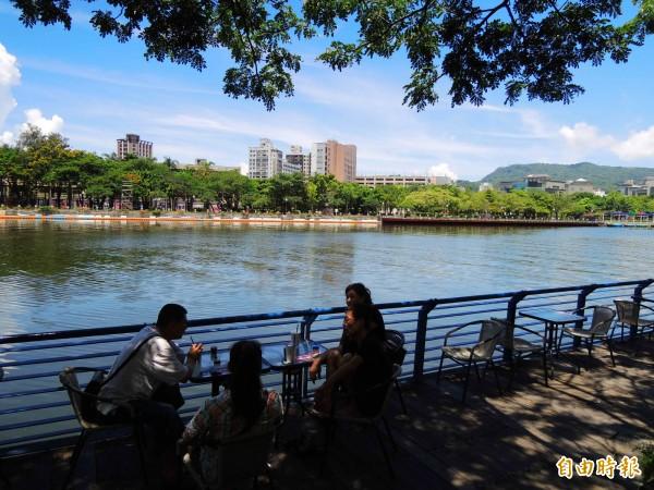 民眾於五福橋旁喝咖啡。(記者黃旭磊攝)