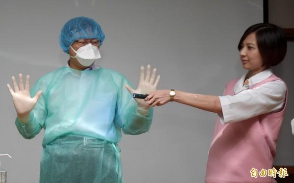 台北市長柯文哲(中)今日視察市立聯合醫院中興院區所舉辦MERS應變演習,並穿著防護服接受檢測。(記者王敏為攝)