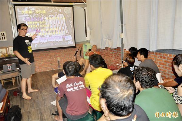 台東女中教師周威同昨晚在晃晃二手書店的三樓地板,與在地大學及高中師生分享反黑箱課綱。(記者黃明堂攝)