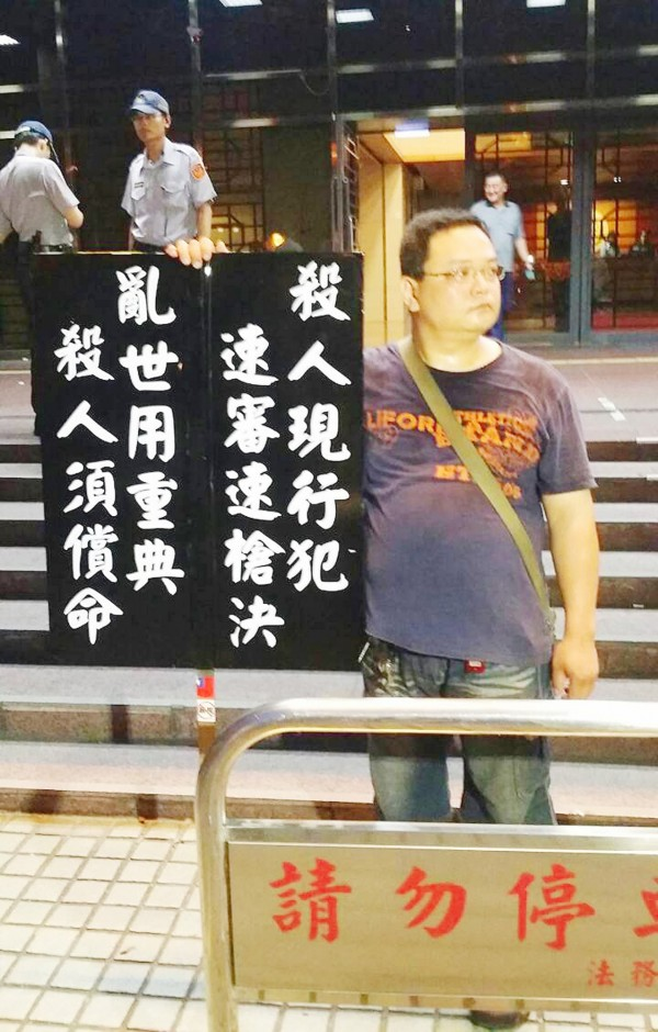 A man holds a sign to show his support for capital punishment in front of the Ministry of Justice in Taipei yesterday. Photo: CNA