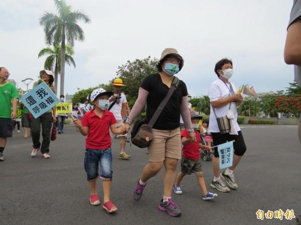 家長帶著小孩戴上口罩一起遊行,訴求「還我呼吸權」。(記者蔡文居攝)