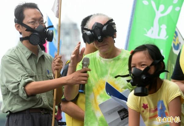 606反空汙全台大遊行台北場,6日在總統府前舉辦「森呼吸健康操」活動,參與的環保團體戴上防毒面具或口罩,要求政府具體改善空氣品質,維護國民健康,包括課徵能源稅、保護樹木等,台灣蠻野心足協會創會理事長學文魯彬(中)致詞時防毒面具一時脫不下來,打趣的表示反正空汙也看不到。(記者簡榮豐攝)