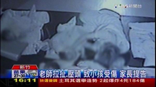 新竹的一家連鎖育嬰中心遭家長投訴,以粗暴方式對待小孩,圖為強壓不想睡的小孩的頭,要他跟著睡覺。(圖擷自TVBS)