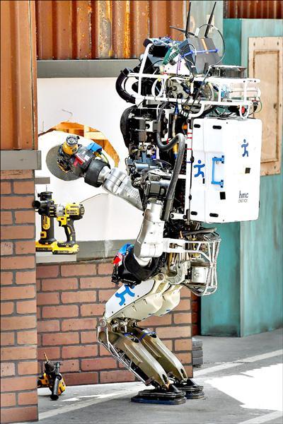 由美國IHMC Robotics團隊所開發的機器人「跑步人」,在決賽中順利的以電動工具開洞。(法新社)