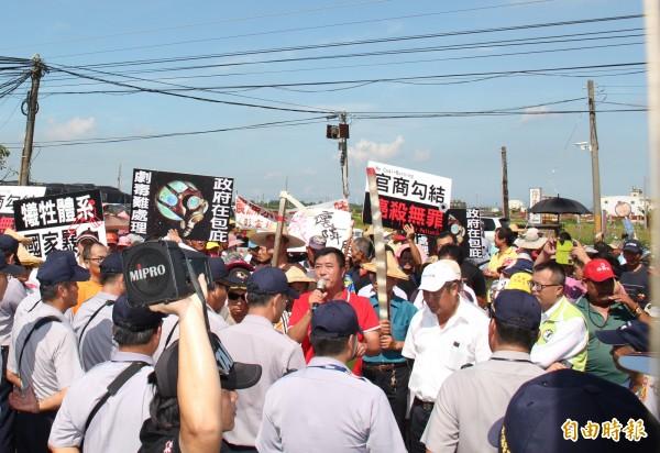 二林榮成紙廠遭300居民包圍抗議,廣興里里長詹金水(紅衣),舉起麥克風要廠方回應污染問題。(記者陳冠備攝)