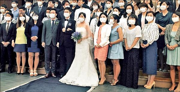 南韓一對新人6日在婚禮上與賓客合影,新郎、新娘和賓客都戴著口罩,可見南韓民眾對當前MERS疫情的憂慮。(法新社)