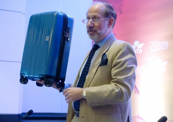 温穆勒親自展示IATA所提出的新登機箱大小。(法新社)
