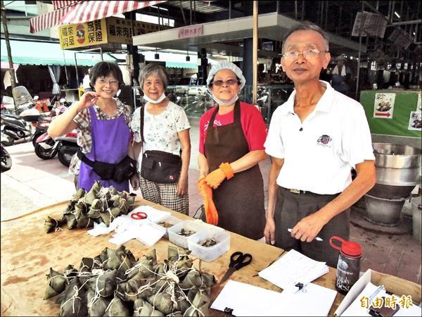 丁萬富、吳秋金(右二)夫妻與一群義工朋友,每年端午節前在虎尾德興市場義賣素粽。(記者黃淑莉攝)