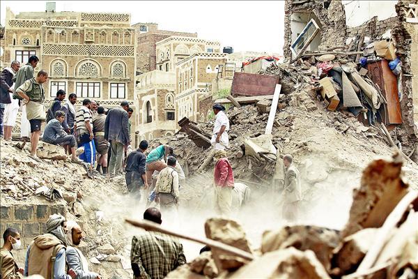 葉門民眾在遭空襲現場的瓦礫堆中,查看是否還有生還者。(法新社)