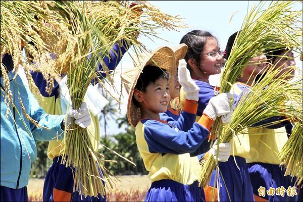 大潭國小畢業生拿著稻穗和空拍機打招呼。(記者陳彥廷攝)