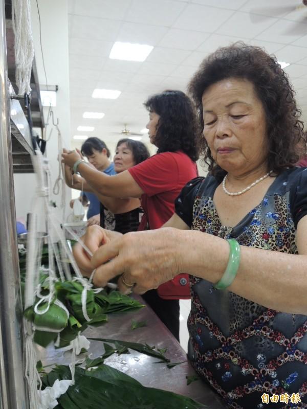 竹崎地區農會內埔家政班的媽媽們包製「晶橙舞、橙圓圓」冰粽。(記者余雪蘭攝)