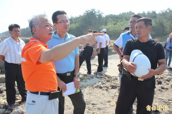竹北市長何淦銘(橘色上衣者)指著山腳澳突堤南側說明他的護岸構想。(記者黃美珠攝)