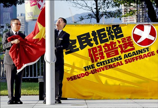 香港立法會十七日將審議攸關特首選舉辦法的政改方案,泛民主派議員已表明將予以否決,警方則動員大批警力,加強立法會戒備,防範反對政改的民眾衝擊立法會。圖為升旗手十六日將立法會外的一面中國國旗降下,一旁則是泛民主陣營的反政改案廣告。(路透)