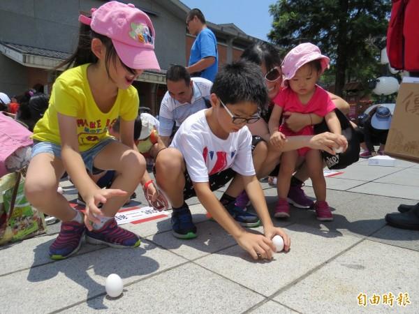 傳藝舉辦立蛋活動,參賽小妹妹成功立蛋,興奮的躍起,和一旁小男生專注立蛋,成明顯對比。(記者王揚宇攝)