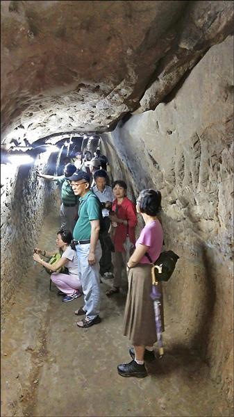 夏聖禮(圖中綠衣者)表示,大坪林引水石腔完全以人力開鑿,工程浩大。(新北市文史學會提供)