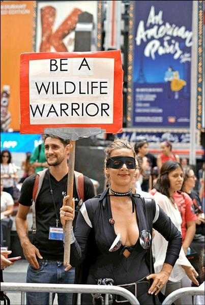 動物保護人士高舉「成為野生動物戰士」的牌子。(法新社)