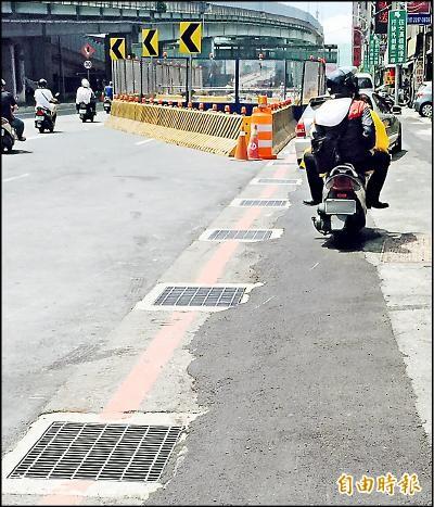 捷運環狀線施工造成多處路段人孔蓋與路面接縫不平,影響機車族通行安全。(記者陳韋宗攝)