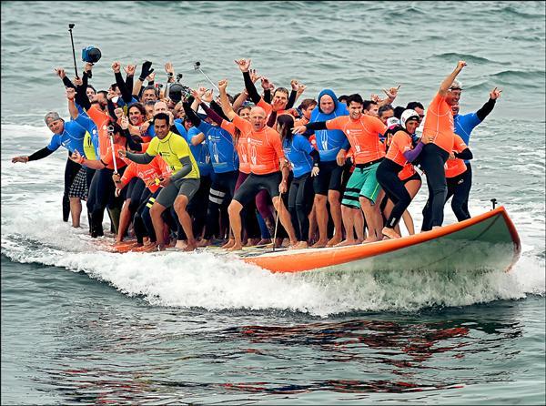 66名衝浪好手同板沖浪,人數刷新金氏世界紀錄。(法新社)