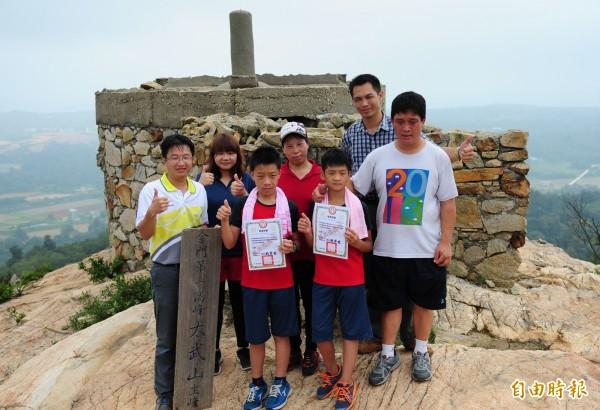 金門述美國小校長劉界宏(前左一)在太武山頂,把畢業證書頒給楊昊龍(前左二)、張煒世(前右二)。(記者吳正庭攝)