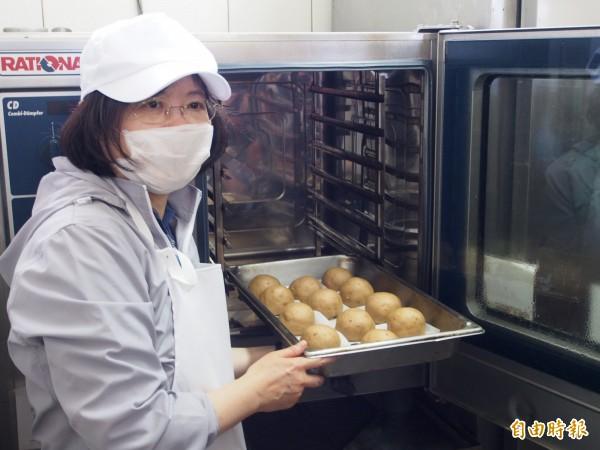 民進黨主席蔡英文將製作好的饅頭放入蒸籠裡,完成製作饅頭的最後一個步驟。(記者王秀亭攝)