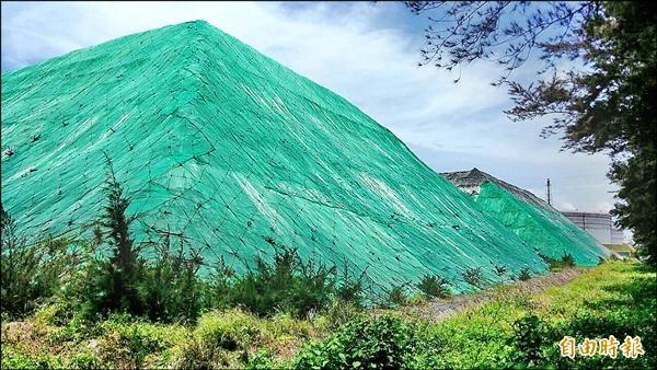 台塑石化燃燒石油焦發電產出的副產石灰,在廠區內堆置成兩座小山。(記者鄭旭凱攝)