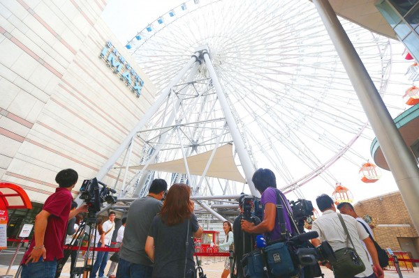 Reporters mill about below the ferris wheel at Miramar Entertainment Park in Taipei's Dazhi area yesterday after the wheel stopped for about an hour due to strong winds. Photo: CNA