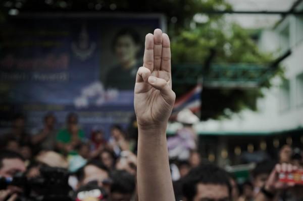 學生模仿電影《飢餓遊戲》,舉起中間3根手指,以示抗議。(法新社)