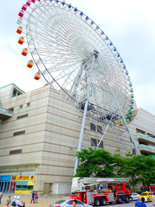A fire engine waits below the ferris wheel at Miramar Entertainment Park in Taipei's Dazhi area yesterday after the wheel stopped for about an hour due to strong winds. Photo: CNA
