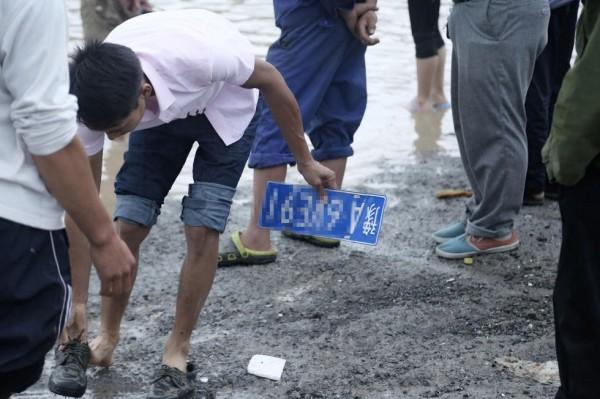 低窪的道路遭雨水淹沒,形成一條大河,部分村民竟藉此做起生意,於水裡打撈被水沖落的車牌,而後向車主收取最高約新台幣473元贖款。(圖取自騰訊網)