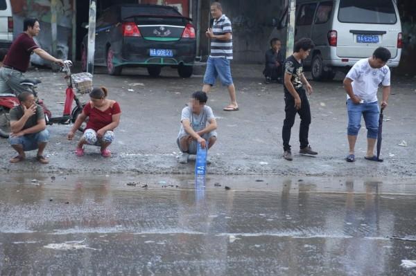 而後經抽水,水位下降,圍觀群眾也散去,唯撈車牌的村民仍在路邊,苦等車主買回。(圖取自騰訊網)