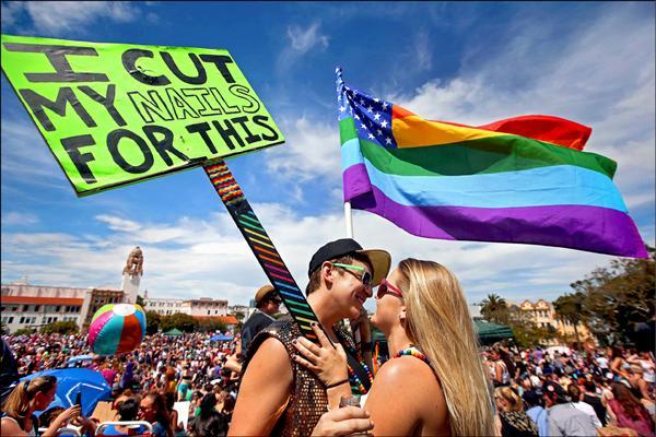 美國最高法院裁決同性結婚全國合法後,加州舊金山二十七日舉辦盛大同志遊行活動,一對同志愛侶開心地親吻對方。不過,遊行的同時,也發生一起槍擊事件,造成一人受傷。(法新社)