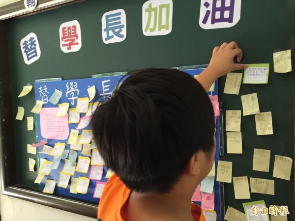 李小弟弟的游姓同學將集氣字條貼上祈福板上。(記者李忠憲攝)