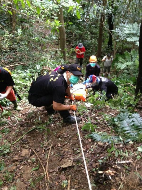 搜救人員利用繩索垂降,把登金面山墜落50米峭壁身亡的王姓山友大體運送下山。(記者李容萍翻攝)