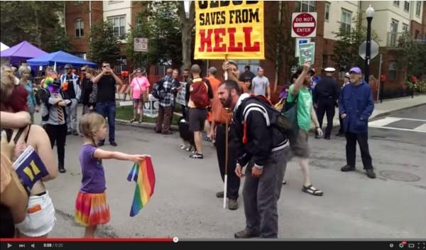 反同志婚姻的男子在街上叫囂,小學一年級的賽亞(Zea),拿著彩虹旗堅定面對、表達立場。(截自影片)