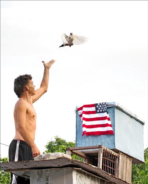 美國總統歐巴馬一日宣布,將在七月中旬與敵對逾半世紀的古巴重啟位於對方首都的大使館,為兩國恢復外交關係跨出重要一步。圖為古巴首都哈瓦那一名男子一日釋放一隻鴿子,鴿籠上方正好披著一面美國國旗。(美聯社)