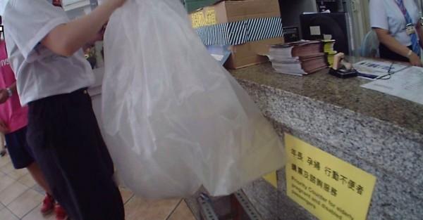 消防隊員到場,嘉義車站服務台人員不疾不徐地拿出一個塑膠袋,裏頭竟裝一隻眼鏡蛇幼蛇。(記者王善嬿翻攝)