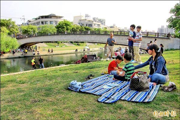 參與屯區野餐生活節,民眾攜家帶眷,在康橋河畔席地野餐。(記者何宗翰攝)