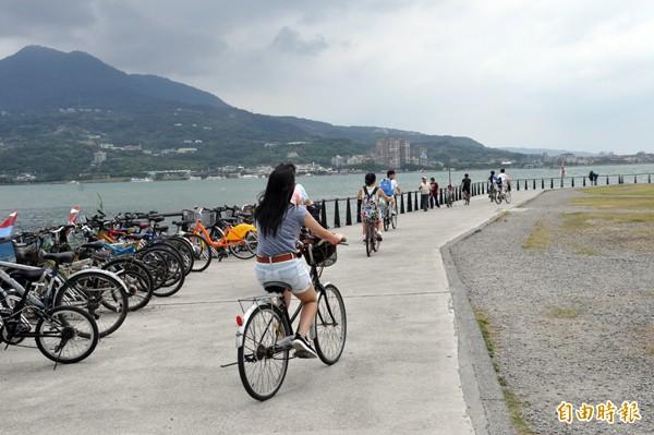 淡水地區下月將建置八處YouBike租借站,圖為民眾在河濱自行車道上騎車情形。(記者郭顏慧攝)
