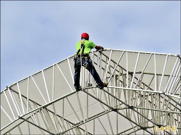 童玩節工人爬上鋼架拆帳篷帆布。(記者王揚宇攝)