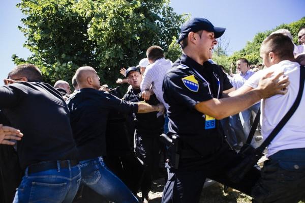 保全人員將情緒激動的民眾架開,場面混亂。(法新社)