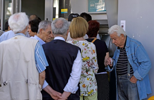 圖為希臘實施資本管制,民眾在銀行的ATM前排隊領錢。(美聯社資料照)