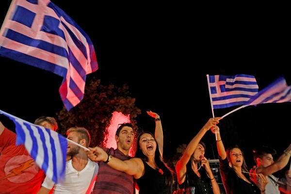 圖為希臘公投反紓困陣營大勝,民眾週日夜晚聚集,揮舞國旗慶祝。(美聯社資料照)