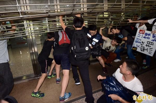 高中生則扛起下降的鐵門,避免同伴被關,現場警力逐漸支援,雙方目前持續對峙中。(記者羅沛德)