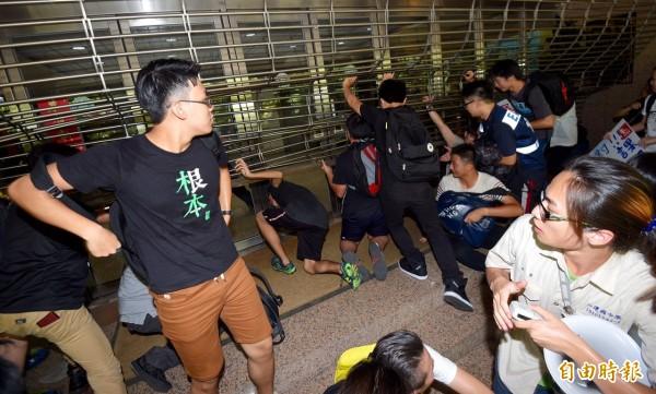 署外高中生則扛起下降的鐵門,避免同伴被關,現場警力逐漸支援,雙方目前持續對峙中。(記者羅沛德)
