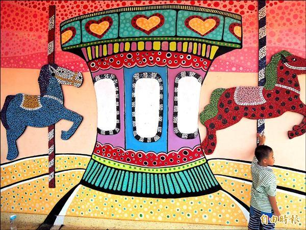 台南善化國小司令台經過設計改裝,搖身變成充滿繽紛色彩的旋轉木馬樂園造型,吸引小朋友的目光。(記者林孟婷攝)