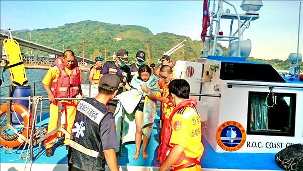 楊女(中)被海巡及消防人員救起,能自行行走。(記者王揚宇翻攝)