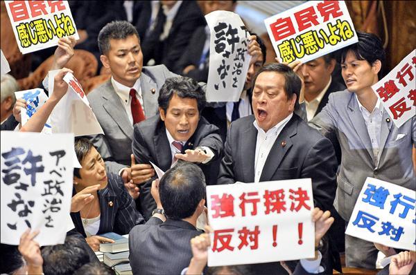 日本安保相關法案15日在眾議院特別委員會強行表決過關,在野黨議員在表決前舉牌抗議,被團團包圍的委員長濱田靖一(右二)露出驚恐表情。(歐新社)