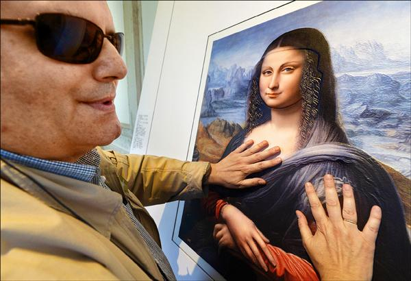 56歲盲人岡薩雷茲在馬德里普拉多博物館藉由觸摸,欣賞義大利藝術家達文西名畫「蒙娜麗莎」複製畫。(法新社)
